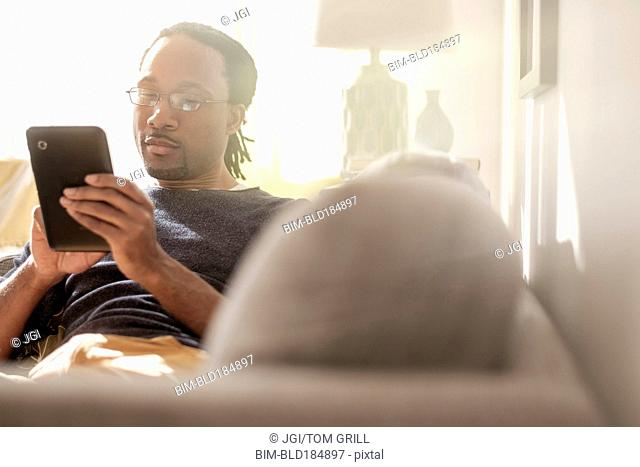 Black man using digital tablet on sofa