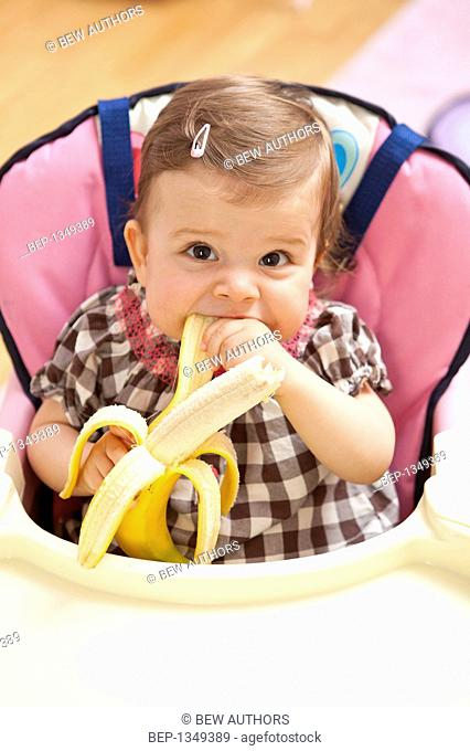 Cute girl sitting in baby-chair, eating banana
