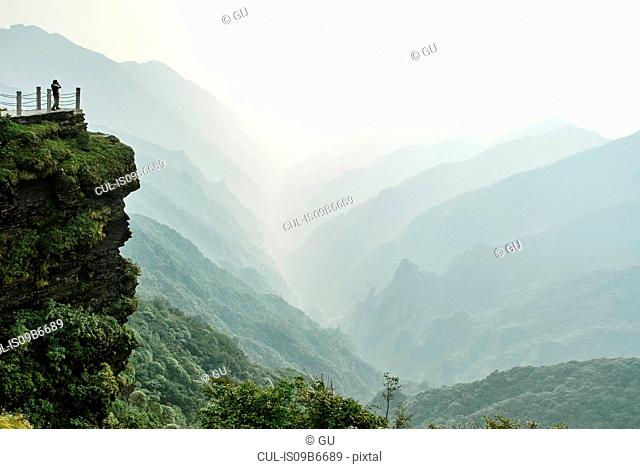 Tourist looking out from Mount Fanjing rock formation, Jiangkou, Guizhou, China