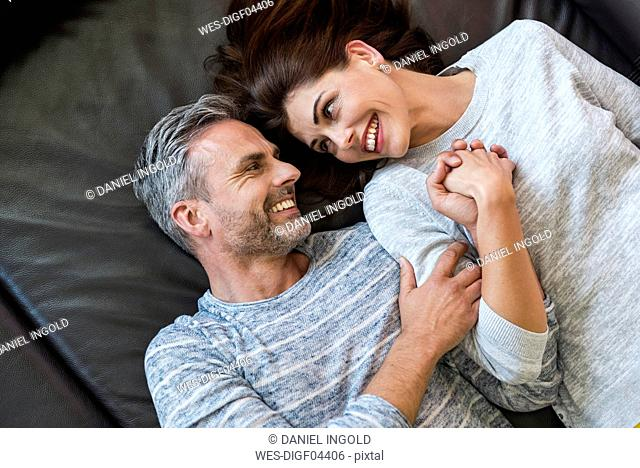 Happy couple lying on couch at home