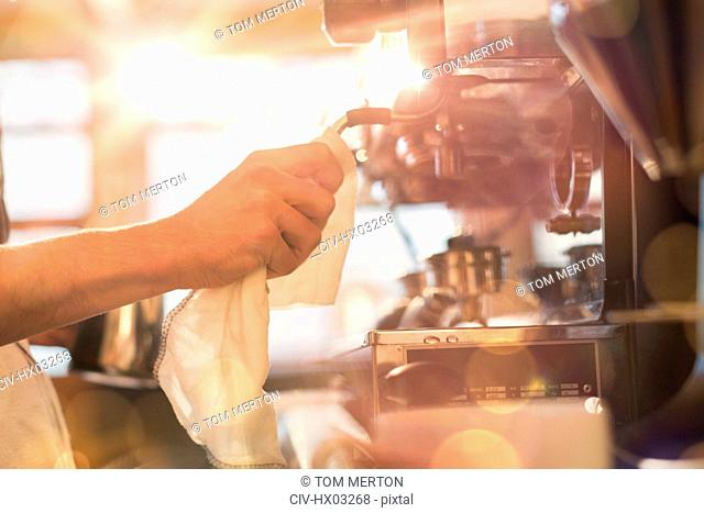 Close up barista wiping down espresso machine milk frother with rag in cafe