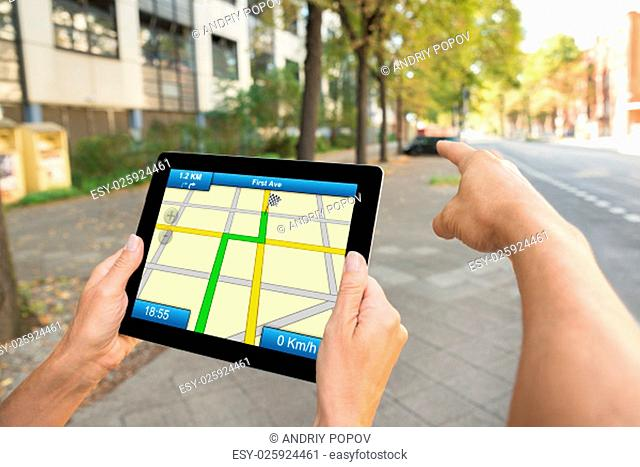 Close-up Of Two People Hands Using Gps Map Navigation On Digital Tablet