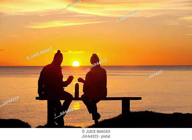 Silhouette of couple, sitting on bench and drinking from thermos, against sunset over the ocean