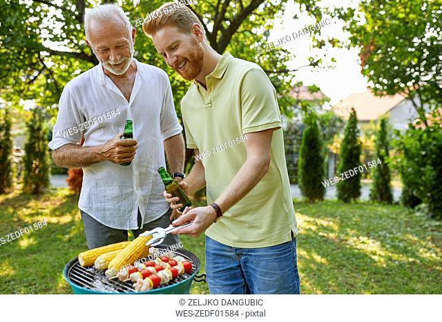 Senior father and adult son having a barbecue in garden