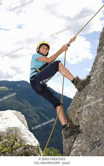 Boy climbing a rock with a rope