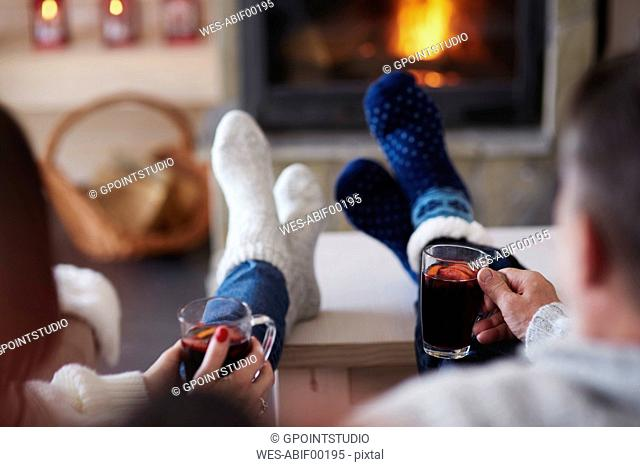 Mature couple with hot drinks in living room at the fireplace