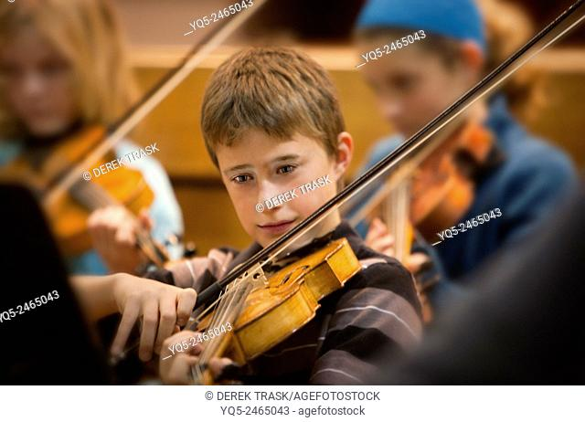boy playing viola in orchestra