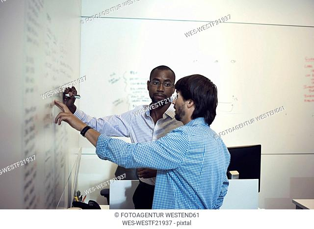 Business people writing on whiteboard in office