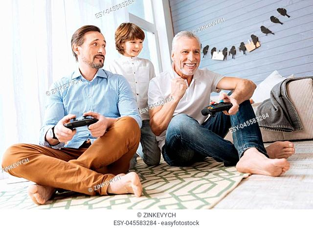 Family competition. Delighted handsome nice men sitting cross legged on the floor and playing video games while having a family competition