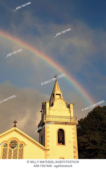 Church of Nossa Senhora das Neves and rainbow on sky after rainshower at Prazeres, Municipality of Calheta, Madeira, Portugal, Europe