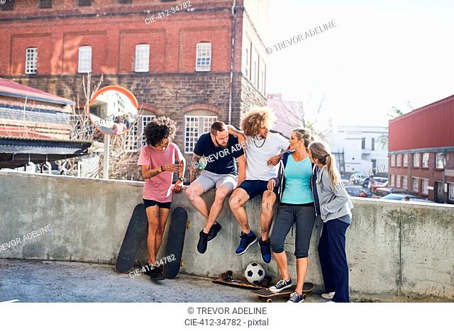 Friends with skateboards hanging out on urban summer wall