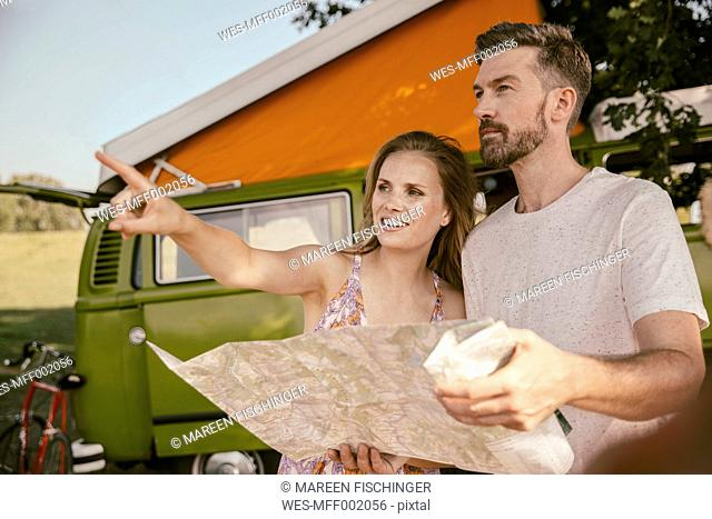 Couple with map in front of van in the nature