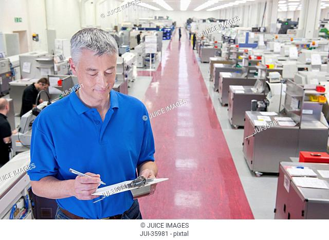 Engineer with clipboard in aisle of manufacturing plant