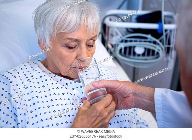 Doctor giving glass of water to seniorB patient