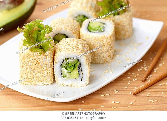 California vegetarian sushi roll with avocado, cucumber and salad. Traditional Japanese rice sushi healthy seafood. White plate, wooden table background