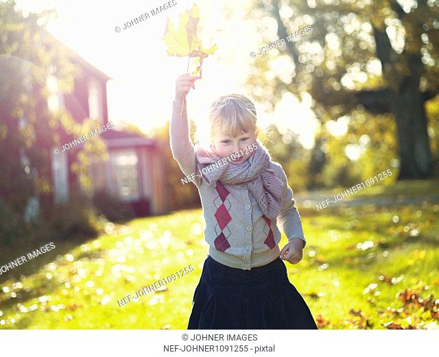 Girl holding autumn leaf in garden
