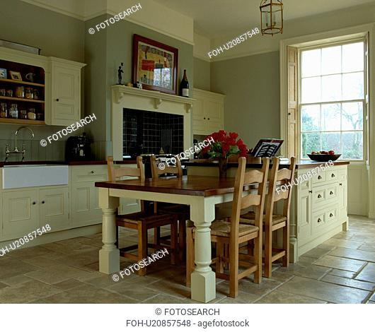 Wooden chairs at fitted table on island unit in grey kitchen with cream fitted units