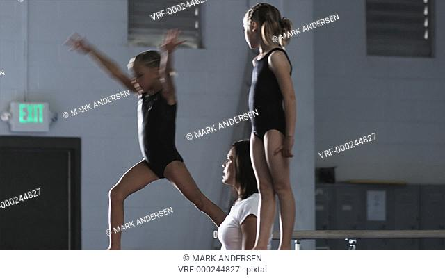 MS PAN Female instructor assisting girls (6-7, 8-9) exercising in gym, Orem, Utah, USA