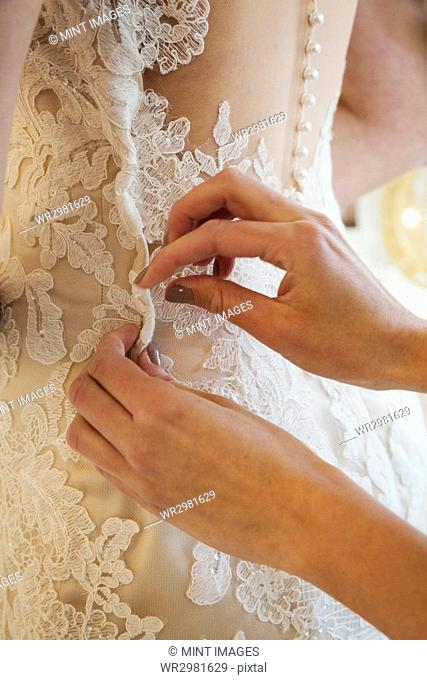 A dressmaker taking in a wedding dress, pinning and fitting it to the client