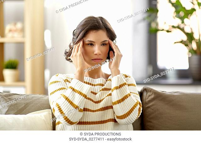 unhappy woman suffering from head ache at home
