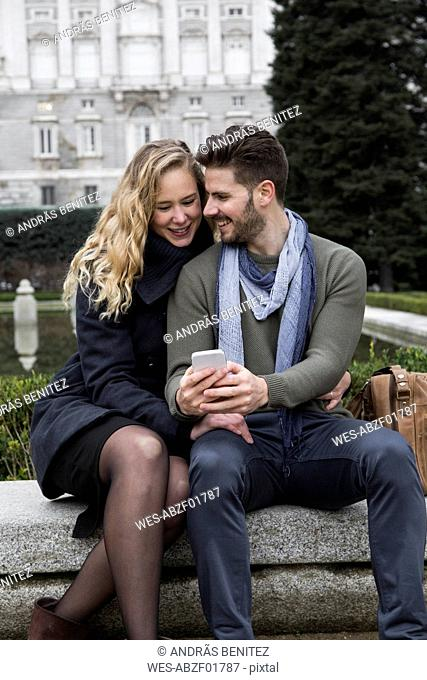 Spain, Madrid, happy couple with cell phone with the Royal Palace in background