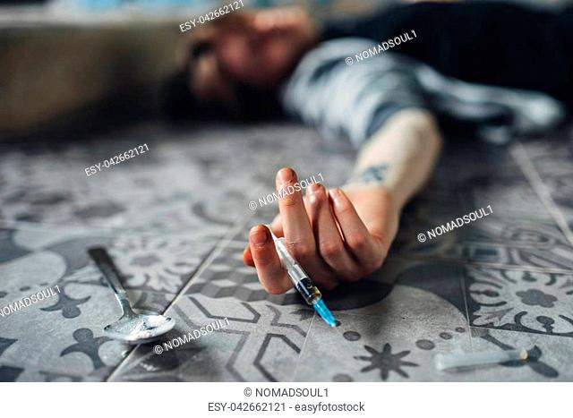 Drug addict lies on the floor, hand with syringe and spoon for dose preparing on the table. Addiction concept, addicted people