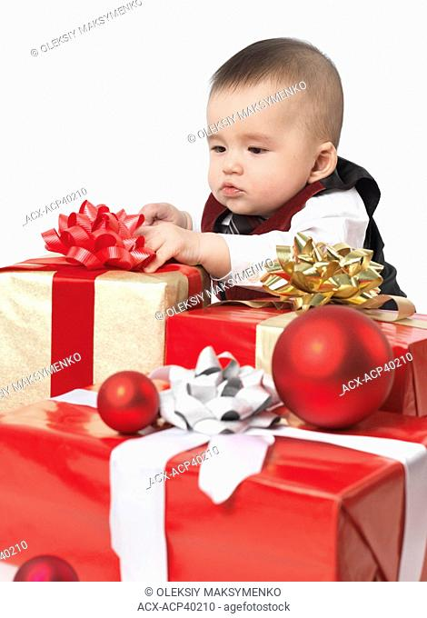Six month old baby boy opening Christmas presents. Isolated on white background