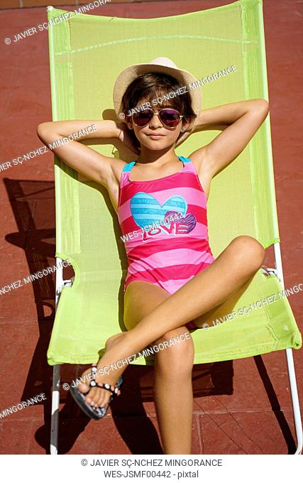 Young girl sitting in sun lounger, sunbathing