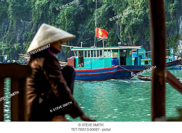 Boat and woman in conical hat at Halong Bay, Vietnam