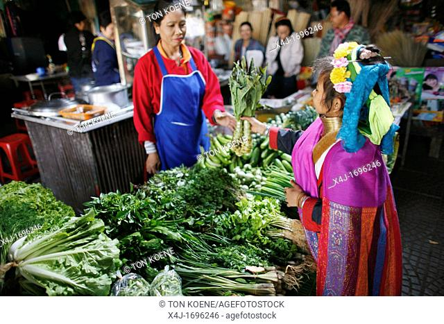 A Longneck girl selects vegetables at a local market Approximately 300 Burmese refugees in Thailand are members of the indigenous group known as the Longnecks...