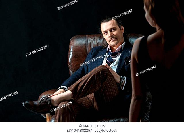 The actor or mature man wearing suit in a classical retro fashion style. The stylish man sitting on a leather couch in a studio