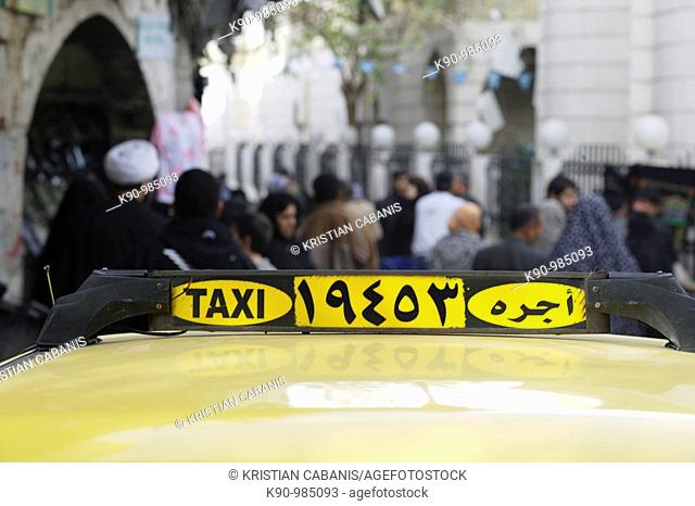 Close up of a taxi sign on the roof of a yellow taxi, standing in a crowd of people, seen in the background, Damascus, Syria, Near East, Asia