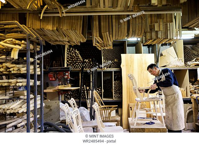 Man standing in a carpentry workshop, working on a wooden chair