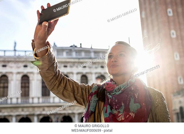 Italy, Venice, Tourist taking pictures with smart phone