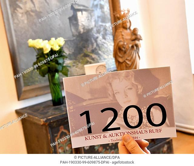30 March 2019, Bavaria, Landshut: Visitors to the auction house take part in an auction of Romy Schneider devotional items