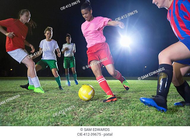 Young female soccer players playing soccer on field at night