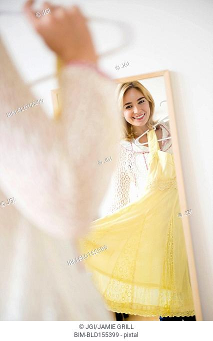 Caucasian woman admiring dress in mirror