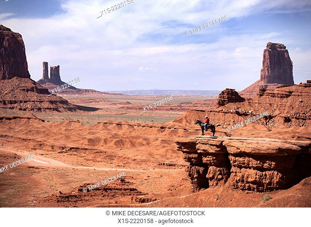 Cowboy on a horse at the edge of a rock mesa looking out to Monument Valley