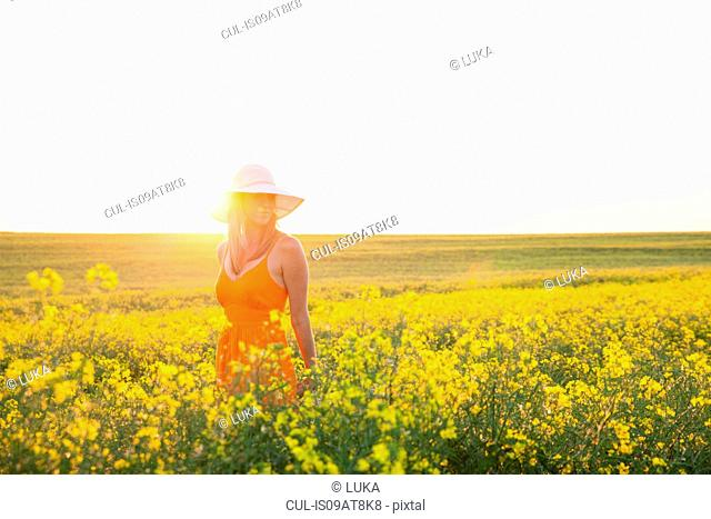 Mid adult woman in canola field wearing sunhat looking away