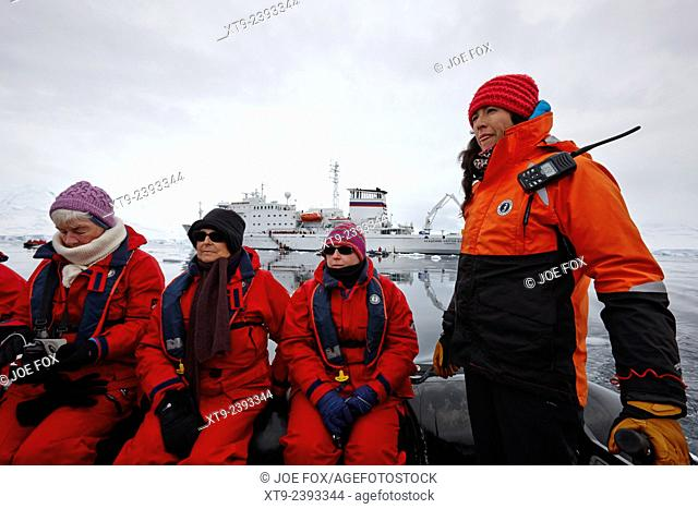 passengers on board a zodiac inflatable with guide on excursion fournier bay antarctica