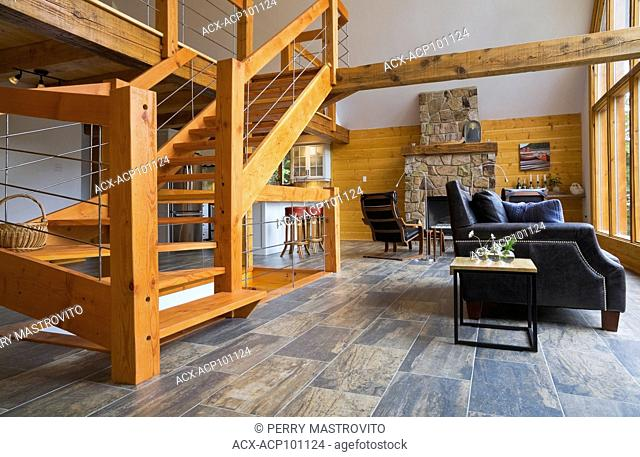 Modern designed pinewood stairs with grey metal railings, black leather sofa and chairs in living room inside a cottage style log cabin, Quebec, Canada
