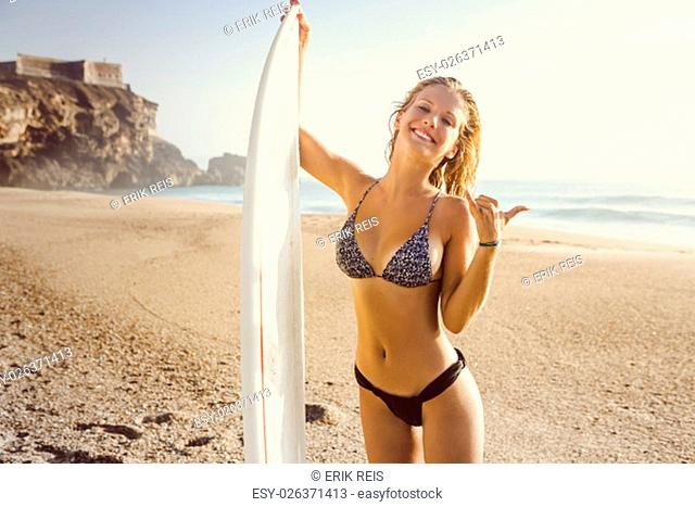 Pretty surfer girl at the beach with her surfbard