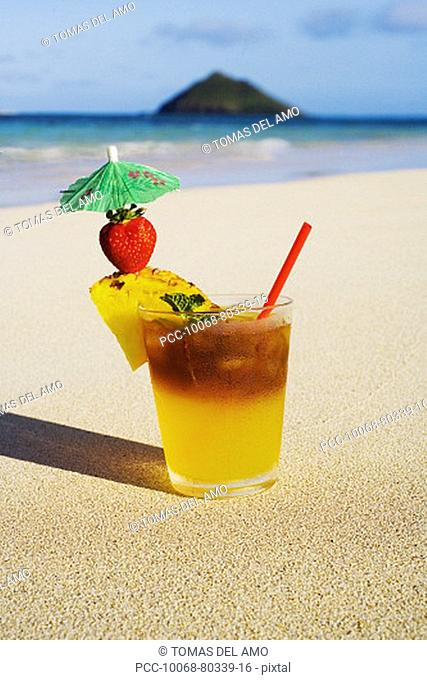 A mai tai garnished with pinapple and a strawberry, sitting in the sand on the beach