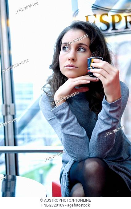 Close-up of young woman waiting in cafe and looking pensive