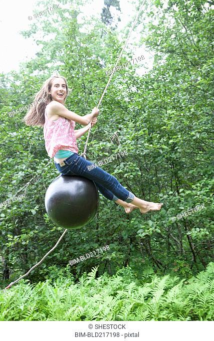 Teenage girl swinging on rope swing