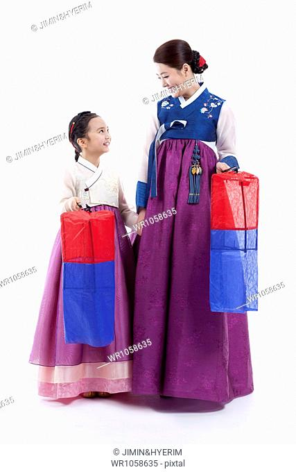 608d76bfc mother and daughter in Korean traditional costume holding traditional lamp