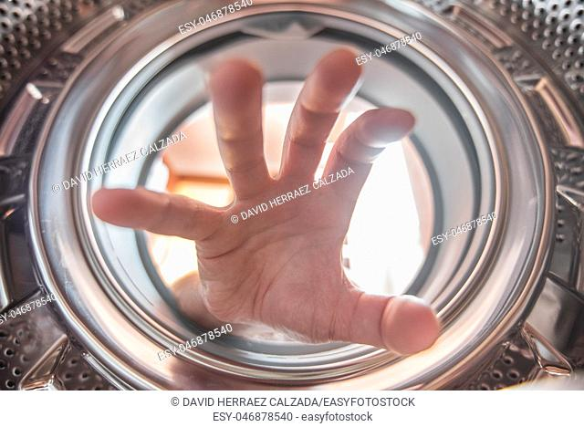 A hand is reaching clothes inside the washing machine