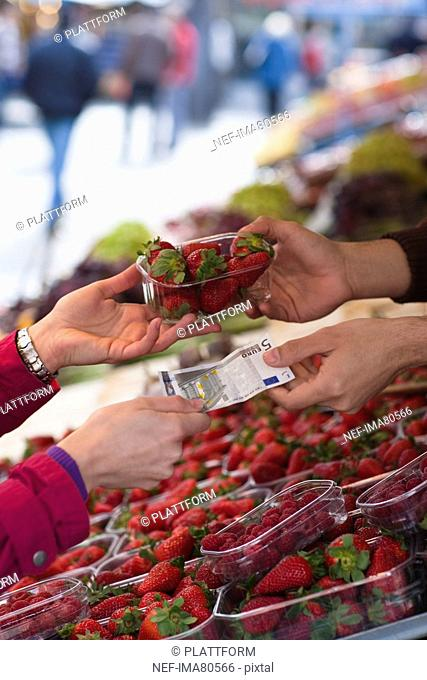 Woman paying for basket of strawberries