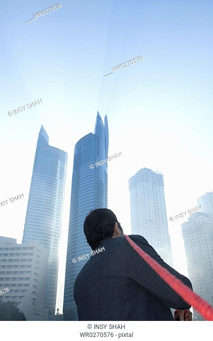 Businessman tugging rope, Towers seen through the mist in the background