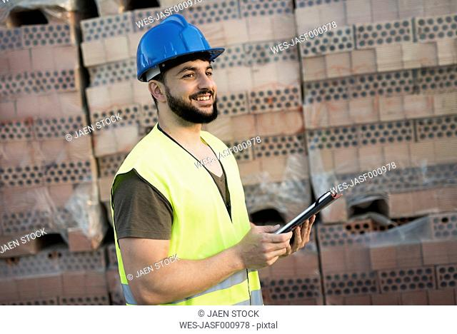 Construction worker in front of packaged bricks